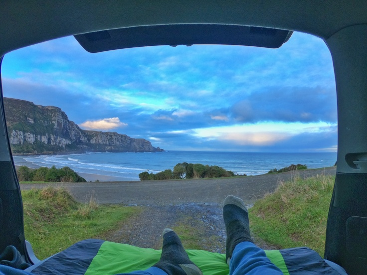 View of Purakanui bay out the back of a car where someone is sleeping