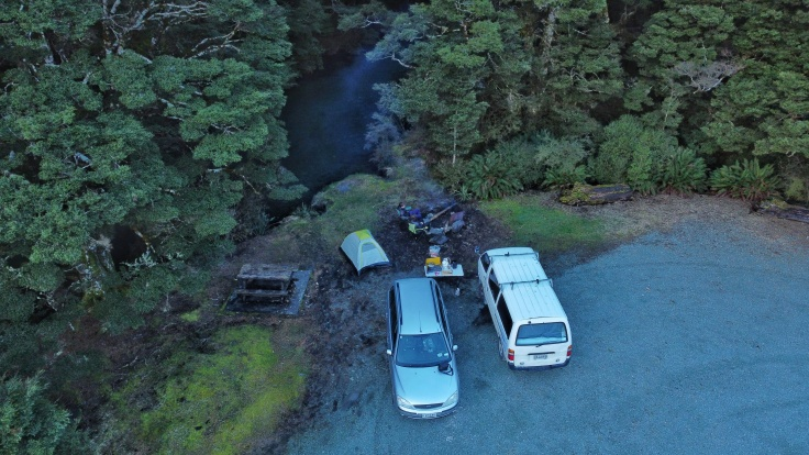 Aerial drone shot of a campsite next to a river and trees while people sit around a camp fire.