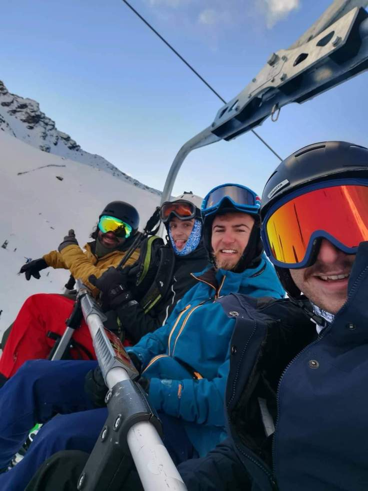 4 male friends on a ski chair lift
